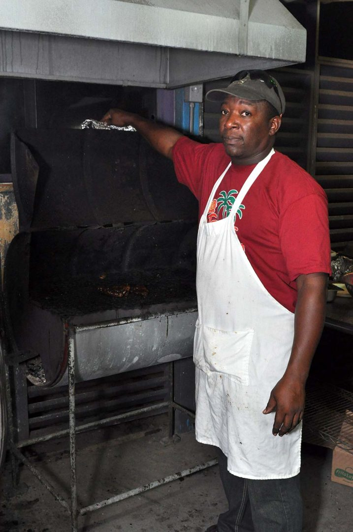 jerk master peter preparing his grill at trellis bay market
