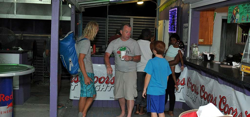 a group of happy customers waiting for their bbq at trellis bay full moon party