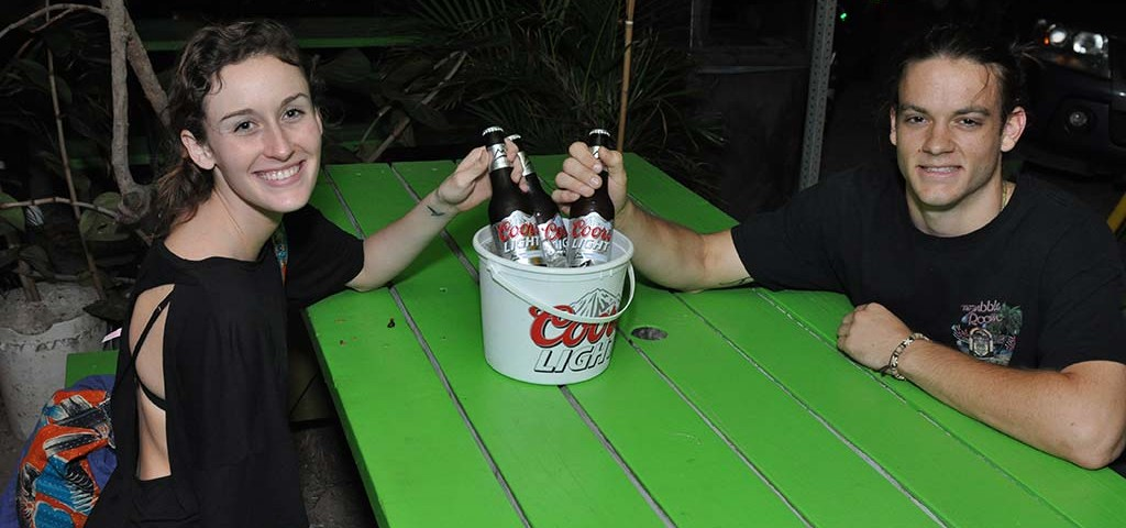tourist enjoying coors lights buckets at trellis bay market